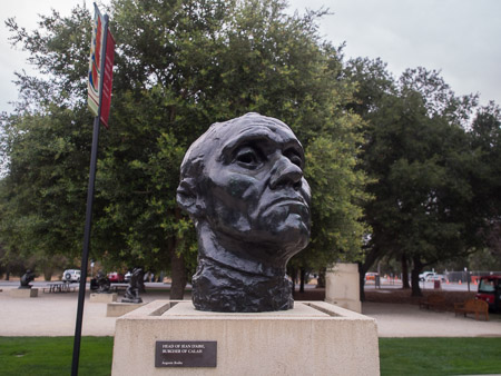 Bronze bust of Jean d'Are, Burgher of Calais. Photo taken several feet away with a wide angle lens. There is a lot of background environment present in the frame.