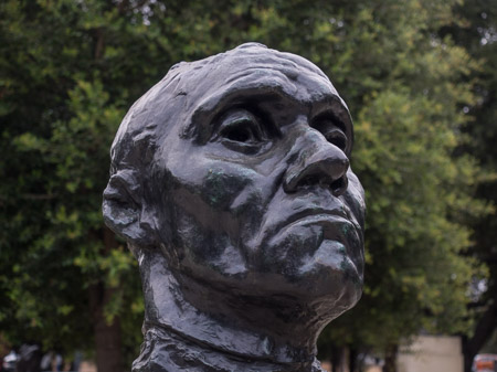 Bronze bust, photo taken several feet away with a normal or 'telephoto' lens. The bust takes up most of the frame and the background is minimized.
