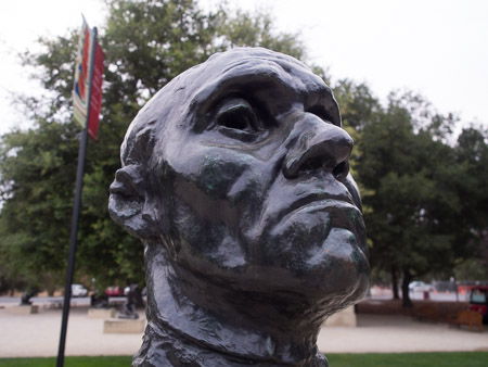 Bronze bust, photo taken just a few inches away with a wide angle lens. The bust takes up most of the frame. There is a lot of background environment present.